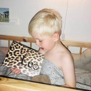 Dreng kigger på bog i seng